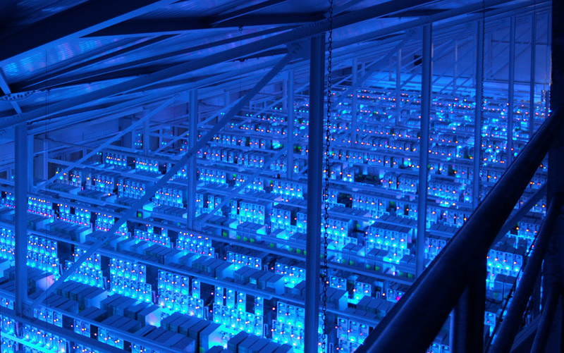 A data center glows blue with the light of thousands of servers