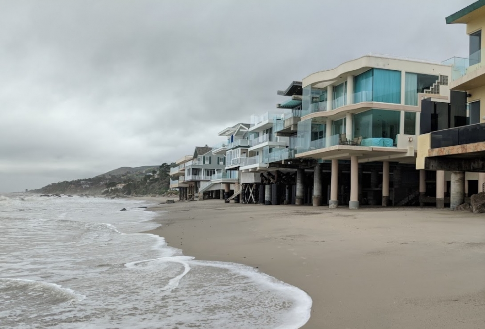 The wash recedes on a sandy beach mere meters from multi-million-dollar beach houses perched upon struts and stilts.