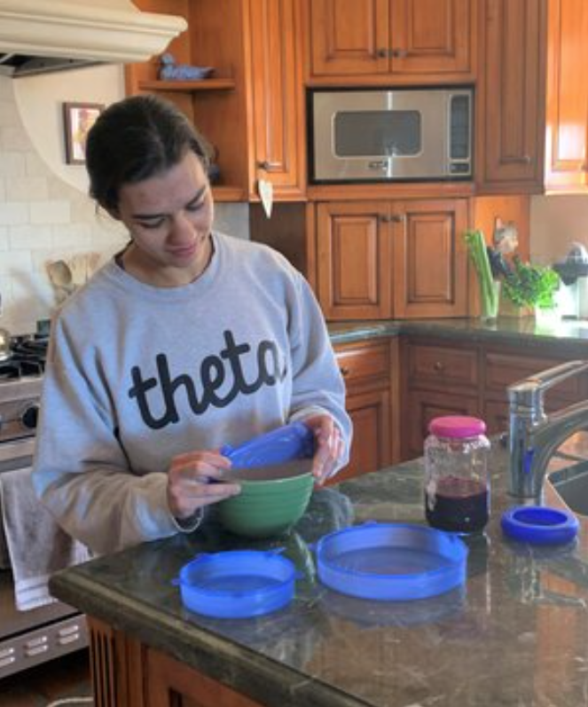 A girl wraps a bowl of food with a reusable silicone lid.