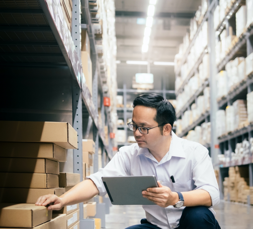 A man in glasses references a tablet while checking items on a warehouse floor.