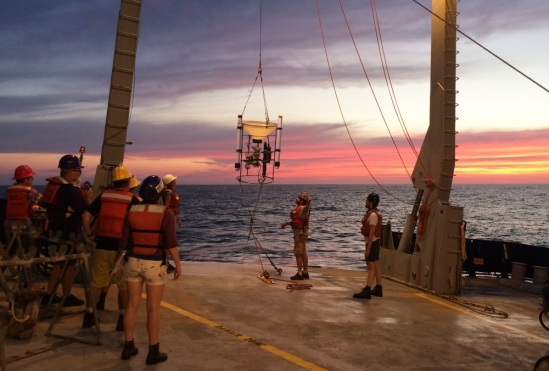 research team lowers a particle collection device into water