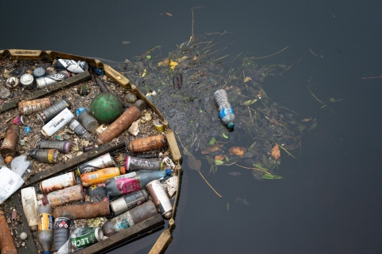 trash collected in a river by a floating boom