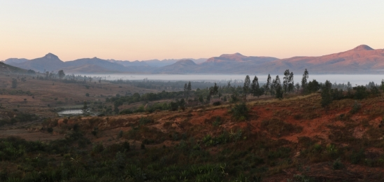 A red landscape dotted with trees. The early morning sun shines on the tops of red mountains in the distance above a layer of mist.