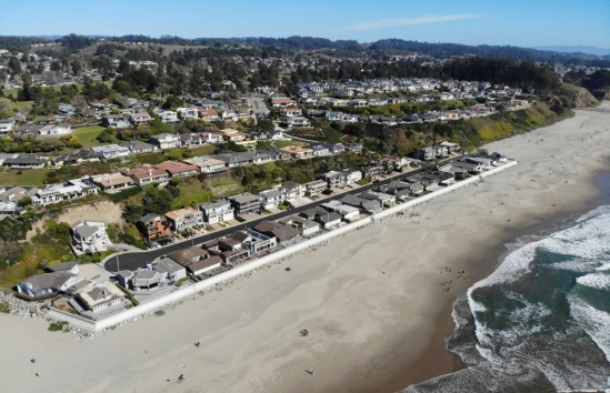 Beachgoers enjoy the shoreline in front of coastal development at Rio Del Mar, Santa Cruz County. A seawall protects the first row of houses from the rising sea.