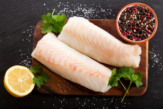 Two fillets of white fish sit on a wooden chop block flanked by a lemon on the lower left, a bowl of peppercorns on the upper right, sprigs of parsley, and a smattering of salt.