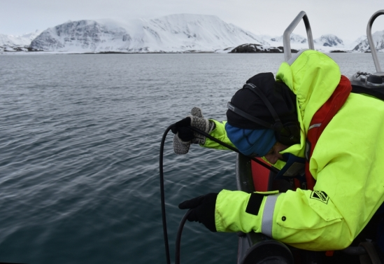 A researcher in a bright yellow/green jacket leans over the side of a boat to lower a microphone into the water
