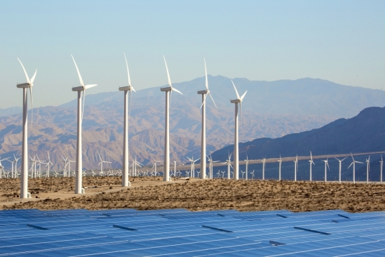 Rows of wind turbines stretch into the California desert with mountains in the background and solar cells in the foreground.