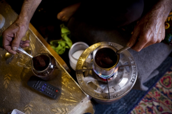 A Syrian refugee makes coffee in a disused building in Lebanon