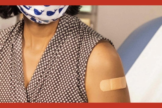 Woman in face covering with a post-vaccination bandage