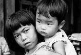 An Okinawan girl carrying her baby brother, by Charles Gail
