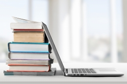 Open laptop and stack of books