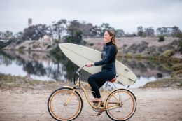 UCSB student with surfboard riding bike near campus lagoon