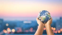 Child holding up earth, cityscape in background