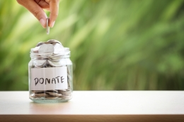 Hand putting coins in a donation jar
