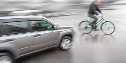 A silver SUV nearly collides with a cyclist.