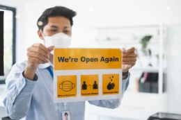 man putting up open sign on business