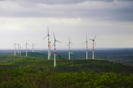Giant wind turbines tower over a lush landscape that stretches off into the distance.