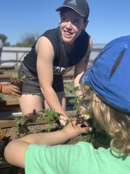UCSB student Caroline Conrad planting with kids at Edible Campus Student Farm