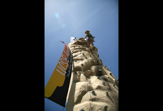 photo of man at the top of a rock climbing tower