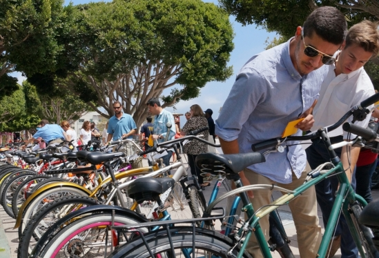 photo of people inspecting used bikes