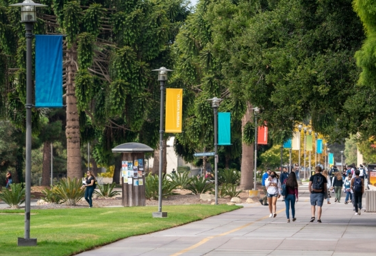 UCSB students walking on campus under colorful banners