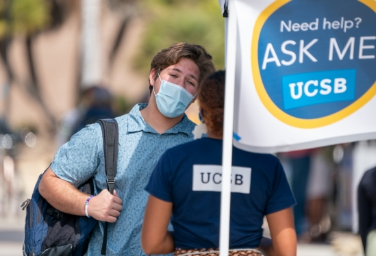 UCSB student in mask asking for help at informational kiosk during 2021 move-in