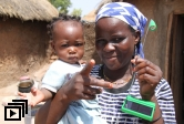 A Ghanaian mother and daughter with a solar light