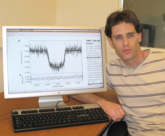 Avi Shporer with a graph that shows how the observed light intensity emanating from a star drops when the newly discovered planet moves in front of the star.