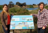 Lisa Stratton, CCBER director of ecosystem management, right, with Jenna Driscoll, from both UCSB's Bren School of Environmental Science & Management, and the Coastal Fund, which funded the new signs.