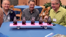 Mathematician Andrew Bernoff (right) demonstrates synchrony using metronomes.