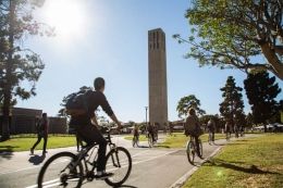 Bicyclists ride in the shadow of UCSB Storke Tower