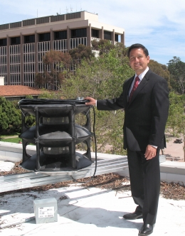 Associate Vice Chancellor Ron Cortez with the Notifier speaker installed on the roof of Kerr Hall.