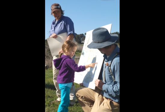 photo of a little girl pointing to a map