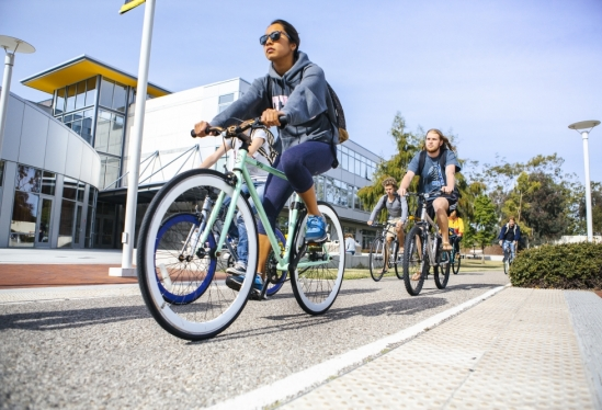 UCSB students riding bikes past Performing Arts