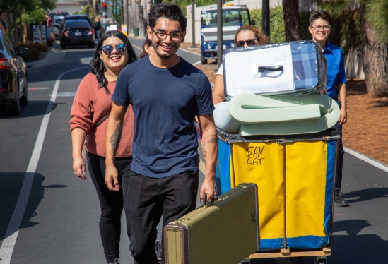 Student with guitar case followed by family during 2018 Move-in at UC Santa Barbara