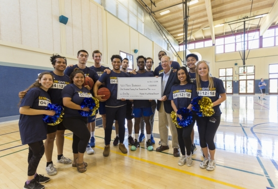 UCSB students, athletes, John McCutcheon holding giant check on Give Day 2018